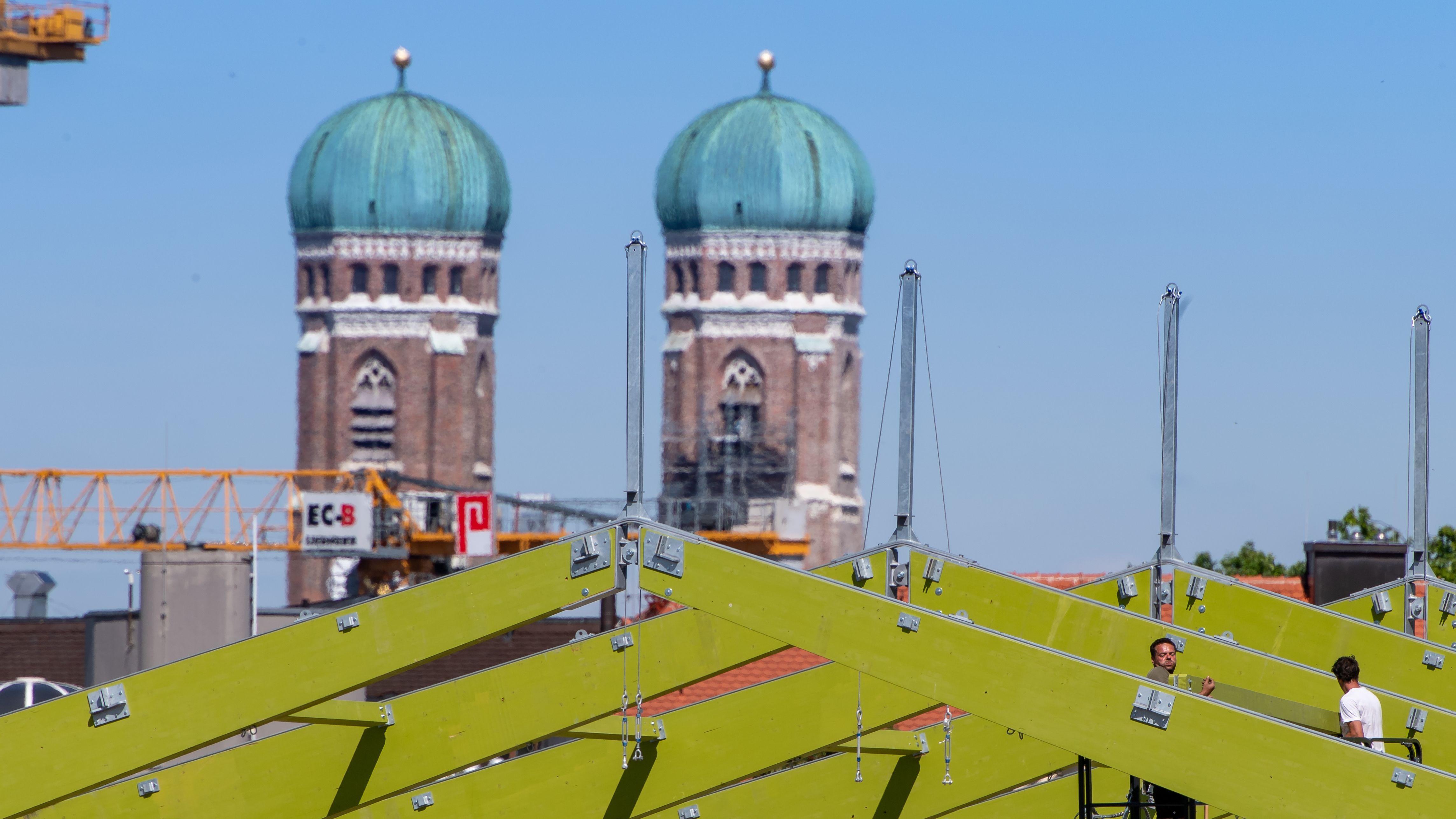 10.07.2019, Bayern, München: Zwei Arbeiter bringen Querbalken in der Dachkonstruktion des Festzelts auf der Theresienwiese an. Im Hintergrund sind die beiden Türme der Frauenkirche zu sehen. Das Oktoberfest beginnt dieses Jahr am 21. September und endet am 06. Oktober.