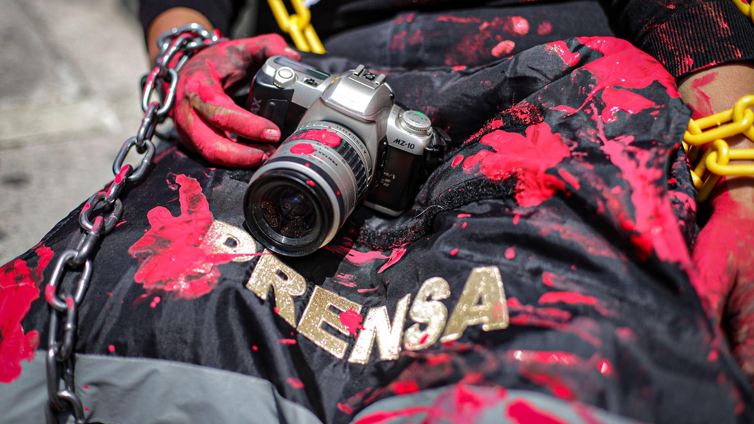 Die Journalistin und Aktivistin Arango hält eine rot verschmeirte Kamera und eine Presseweste bei einer symbolischen Aktion vor der mexikanischen Staatsanwaltschaft gegen die Ermordung des Journalisten Nevith Condes Jaramillo