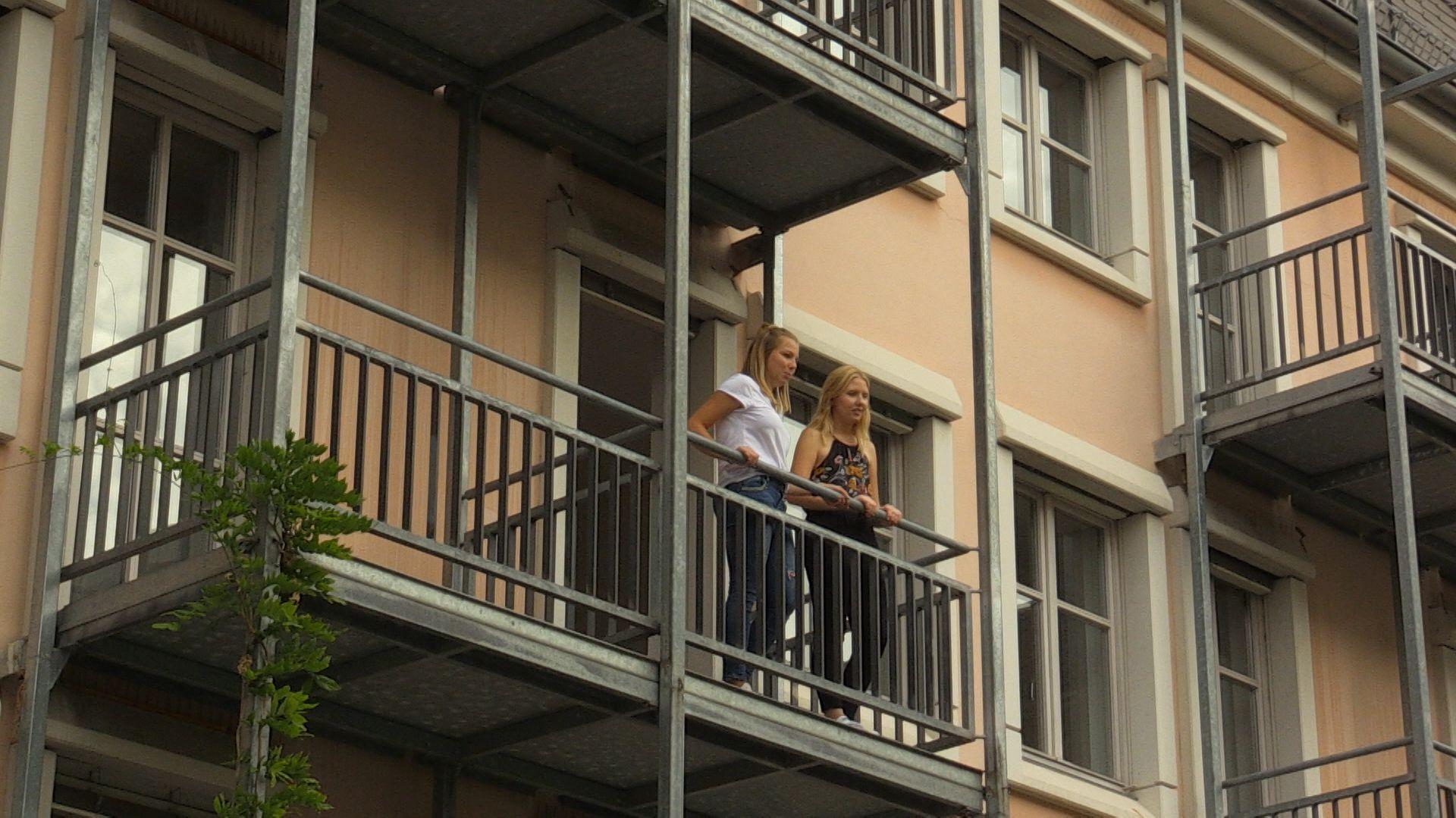 Zwei junge, angehende Erzieherinnen auf dem Balkon einer vergünstigten Wohnung.