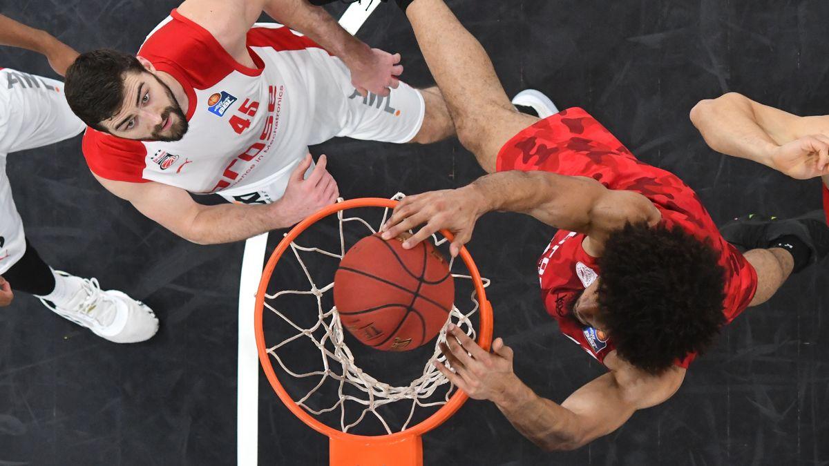 Zwei Spieler unterschiedlicher Teams stehen unter einem Basketballkorb