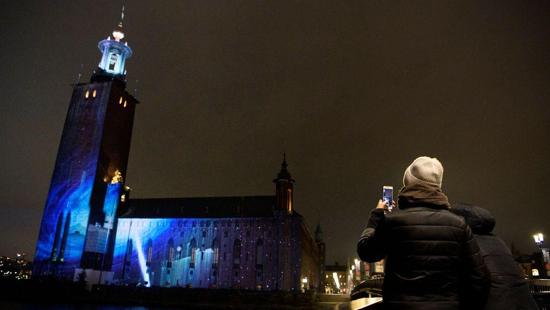 Das Rathaus in Stockholm bei Nacht. Im November 2020 wurde es anlässlich der Nobelpreis-Woche mit einer Lichtinstallation bestrahlt. Eine Touristin im Bildvordergrund fotografiert das Gebäude mit ihrem Handy