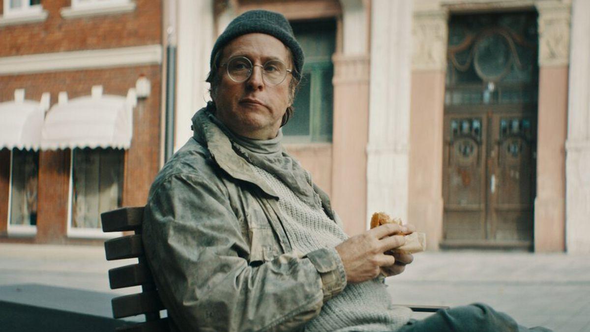 """Ein Mann mit Mütze sitzt auf einem Stuhl auf der Straße und schaut ein wenig provozierend in die Kamera:Bjarne Mädel in """"Faking Bullshit"""" (Filmszene)"""