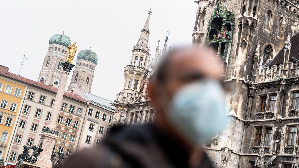 Ein Mann mit Mundschutz vor der Münchner Frauenkirche.