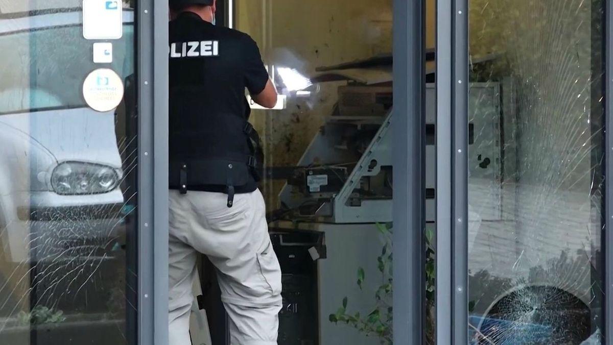 Ein Polizeibeamter steht vor einem gesprengten Geldautomaten in einer Bankfiliale, deren Glastüren beschädigt sind.