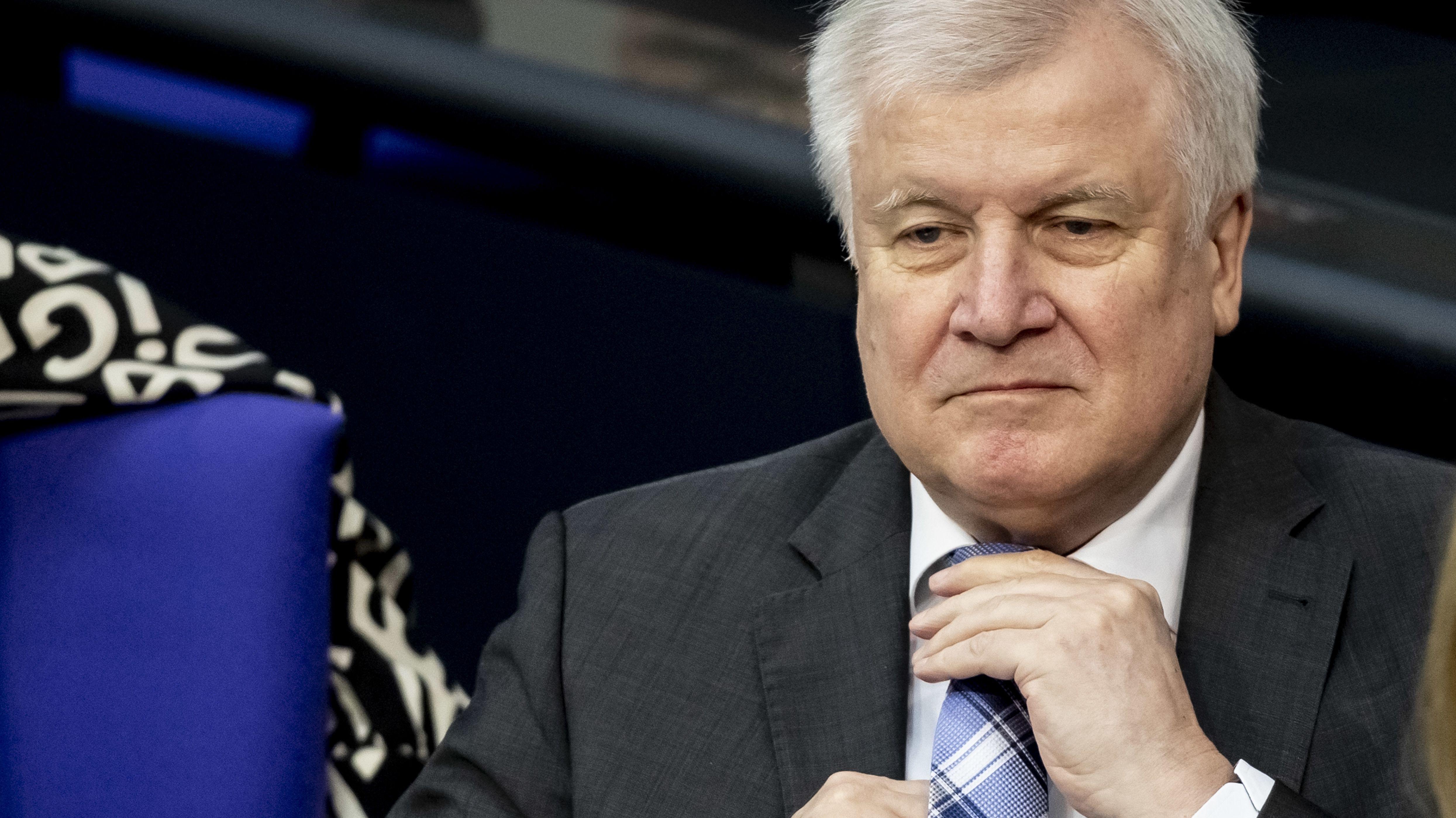 Innenminister Seehofer rückt sich im Bundestag die Krawatte zurecht