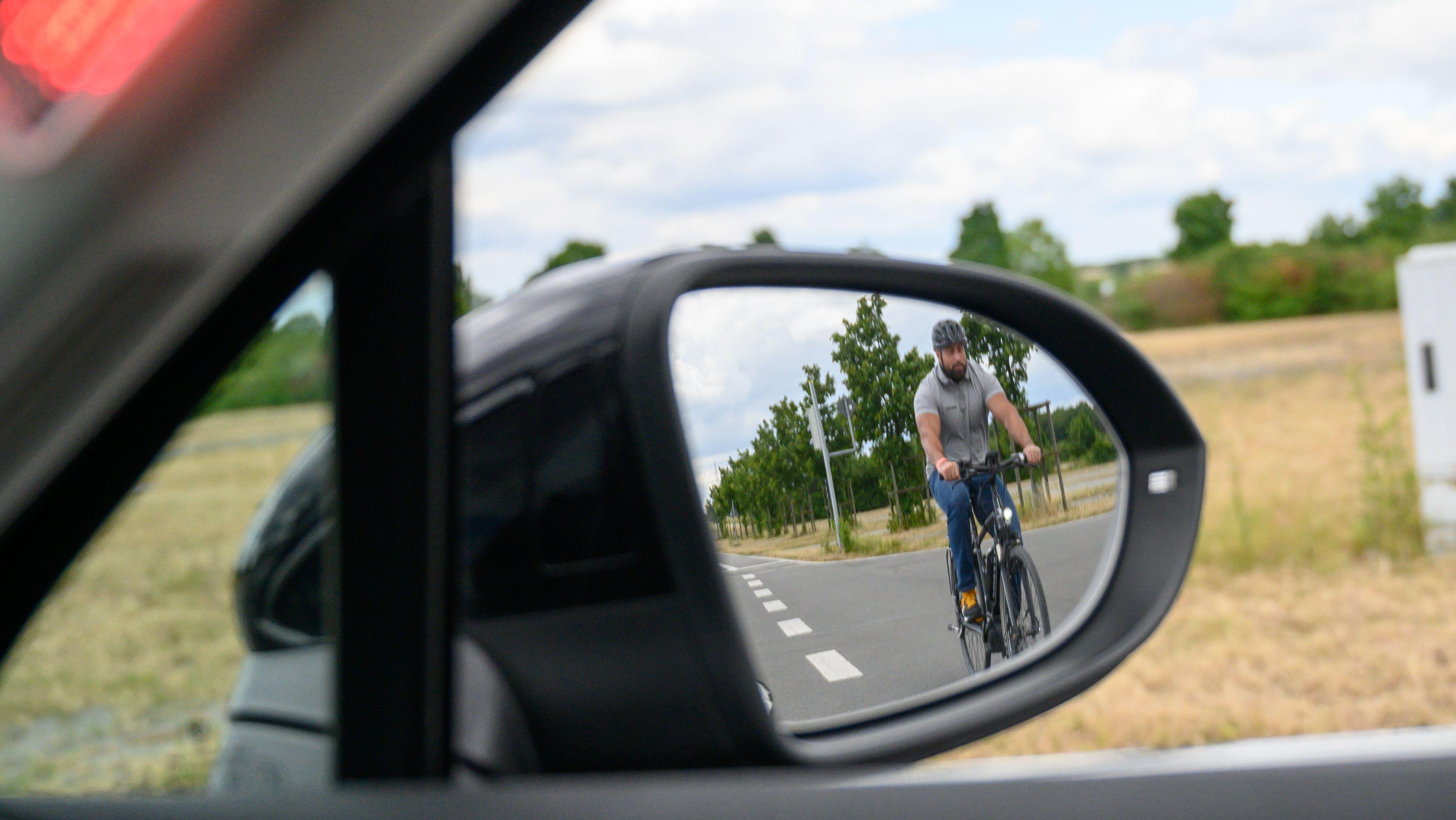 Im rechten Außenspiegel eines Autos ist ein Fahrradfahrer zu sehen, der sich von hinten nähert. Im Hintergrund: Feld und Wiese.