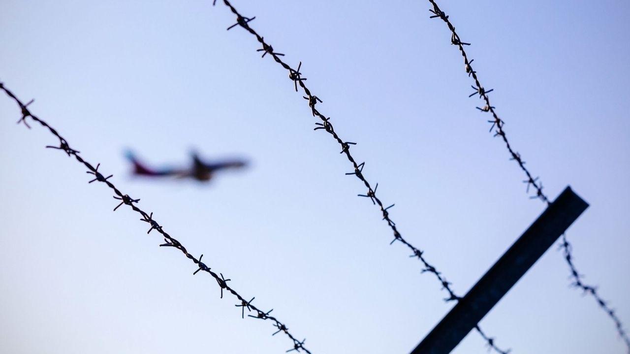Ein Flugzeug fliegt hinter Stacheldraht.