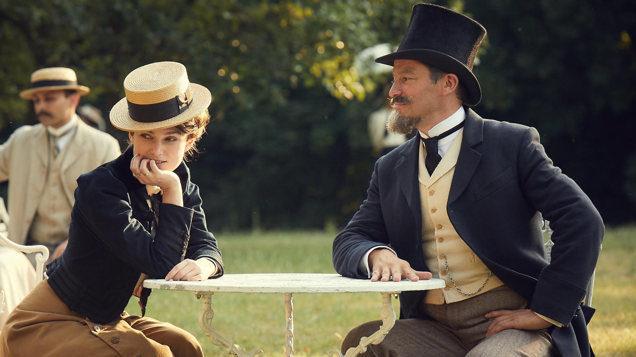 """Szene aus dem Film """"Colette"""": Colette sitzt draußen mit ihrem Mann an einem Tisch. Sie schaut aus dem Bild, er schaut sie an."""