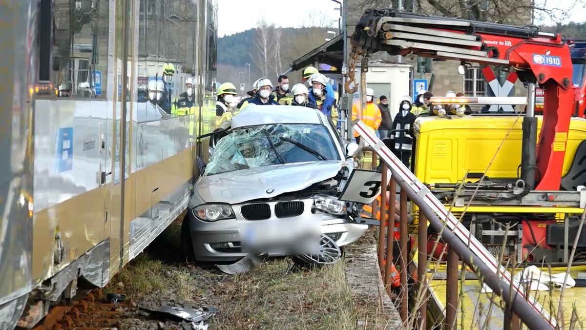 Ein demoliertes Auto steht neben einem Zug im Gleisbett.