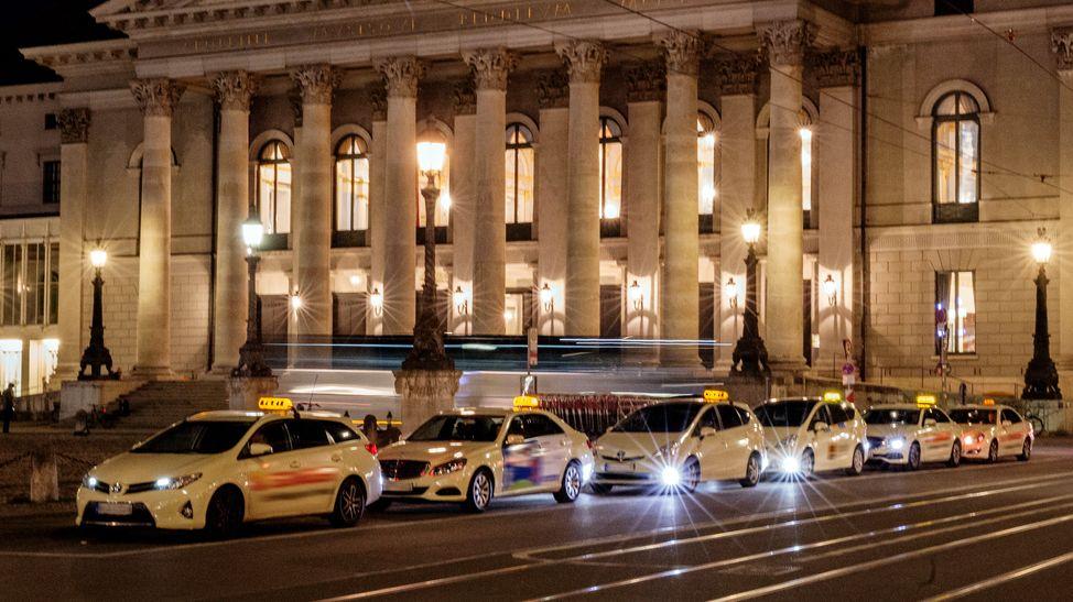 Mehrere Taxis warten nachts vor dem Münchner Nationaltheater auf Kundschaft