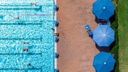 Das Straubinger Freibad von oben. Links das Schwimmbecken, rechts aufgespannte, blaue Sonnenschirme. Mehrere Menschen sind beim Schwimmen oder Sonnen zu sehen.    Bild:dpa / Armin Weigel