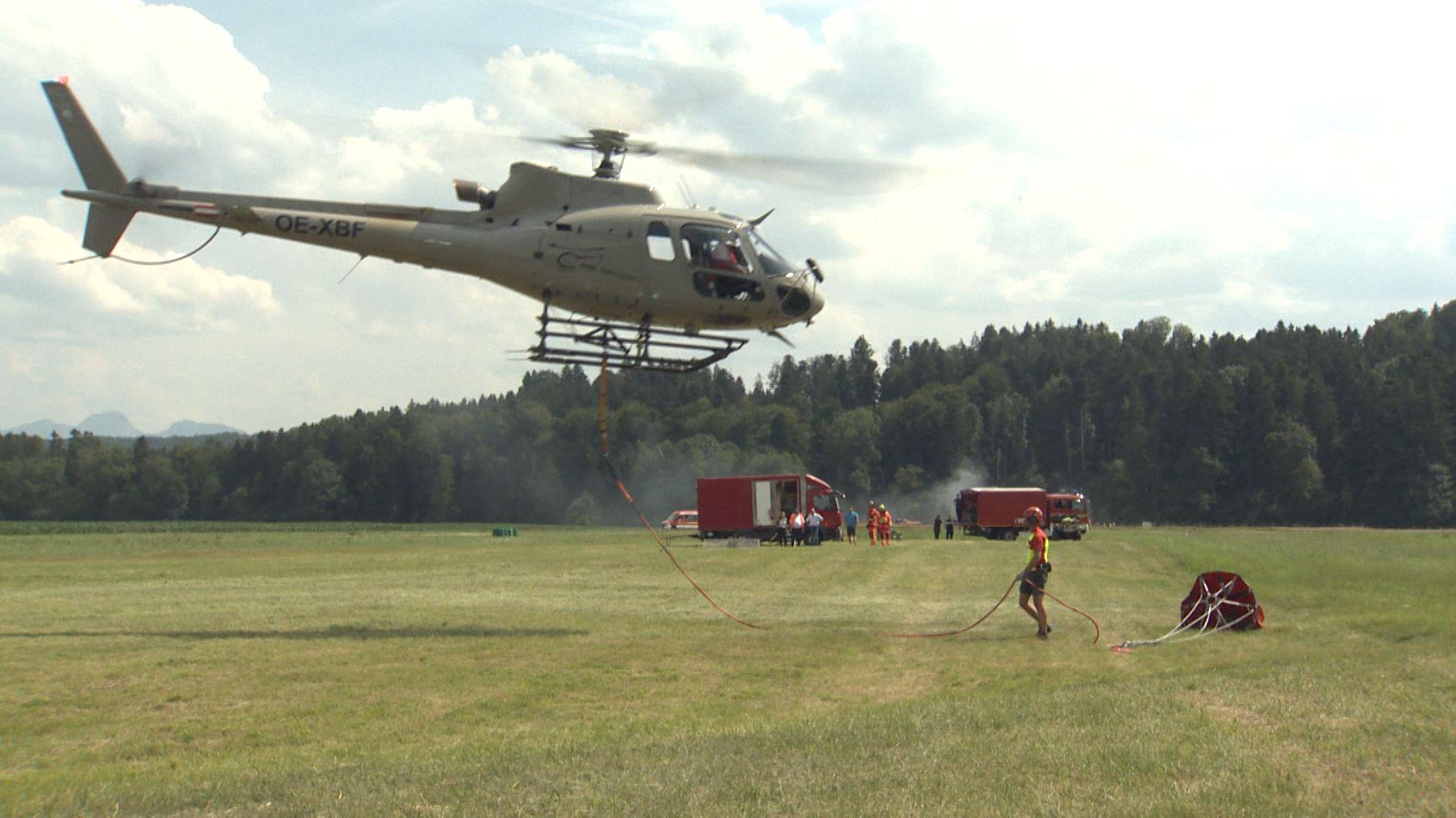 Hubschrauber schwebt wenige Meter über einer Wiese, im Hintergrund Feuerwehr und Rauch