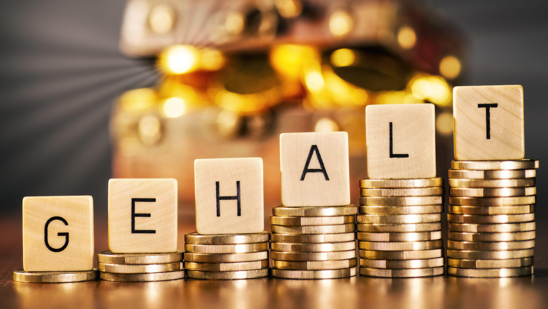 Das Wort Gehalt auf ansteigenden Stapeln mit Münzen vor einer Truhe mit Geld