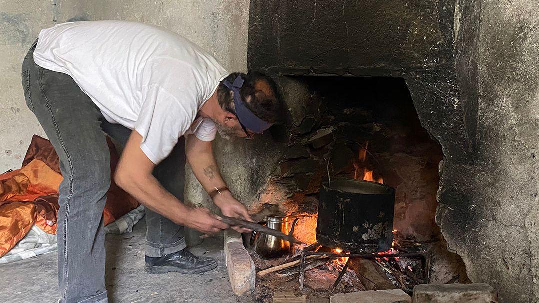 Xhevdet Pashaj schürt das Feuer. Die Männer essen nicht, aber sie trinken Wasser und kochen sich Kaffee