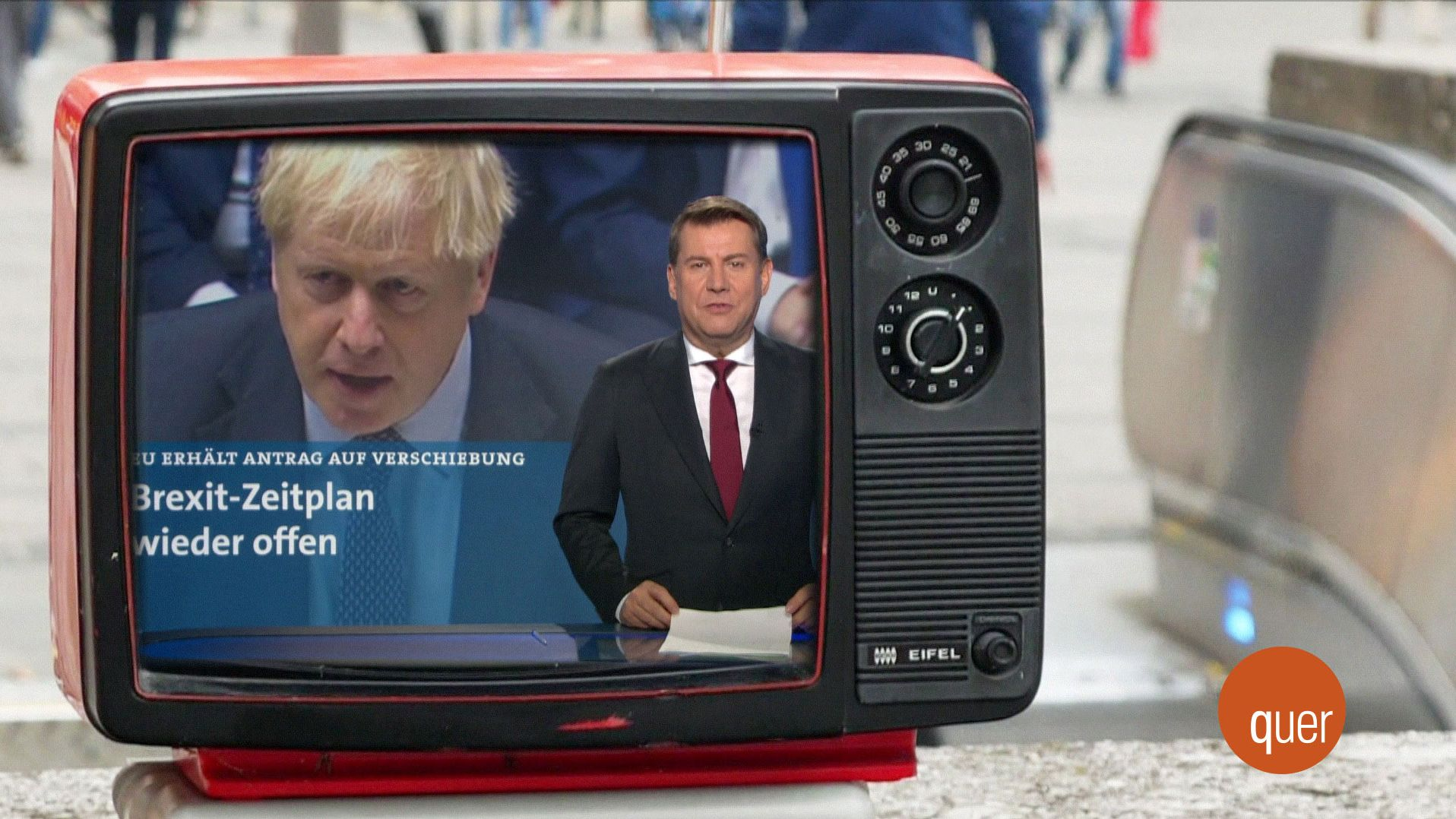 Ein Fernseher, auf dem ein Nachrichtensprecher und der britische Premierminister Boris Johnson zu sehen sind.