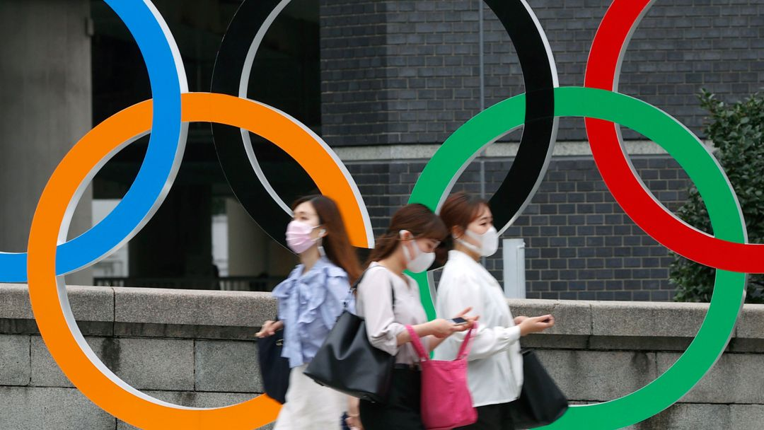 Japan, Tokio: Menschen mit Gesichtsmasken gehen an der Statue der Olympischen Ringe in Tokio vorbei.