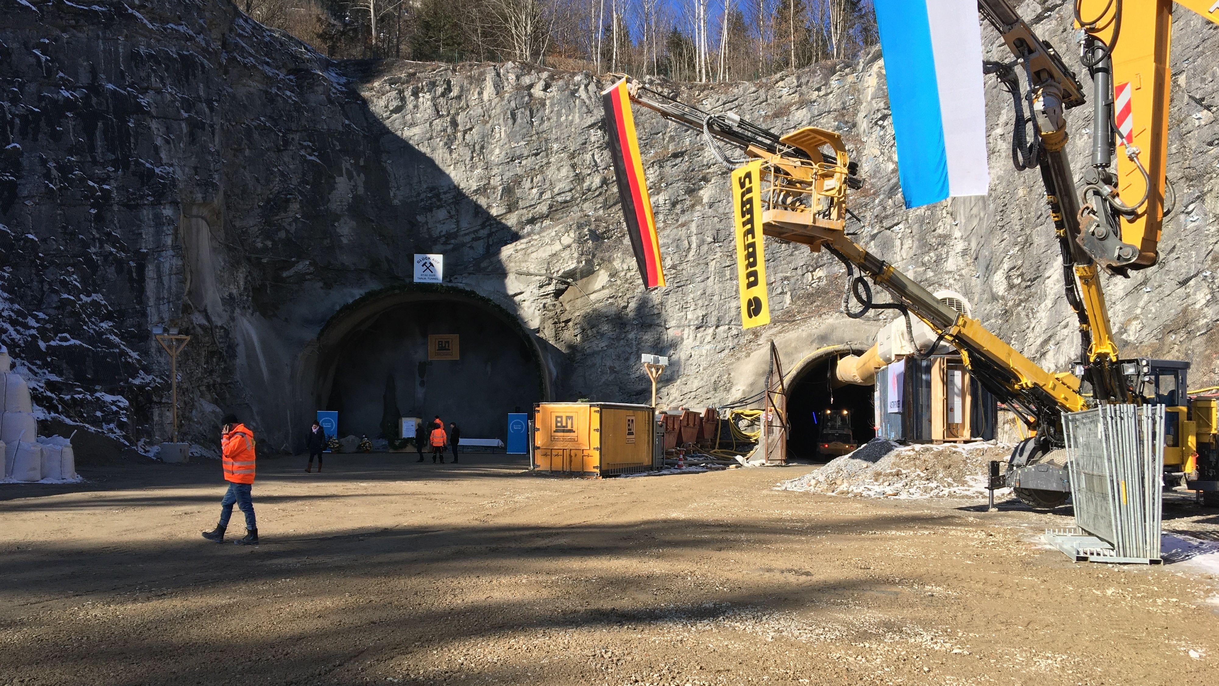 Bauarbeiter und Fahnen am Nordportal des Kramertunnels in Burgrain.