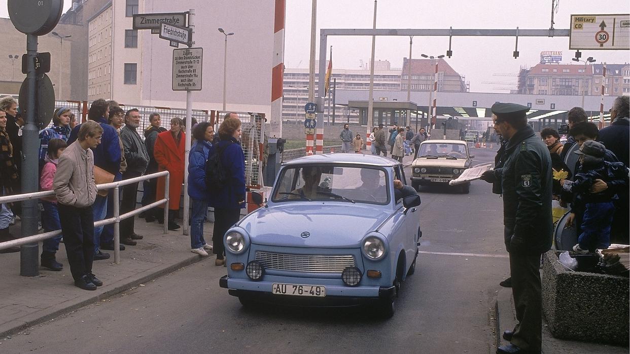 Ein blauer Trabi fährt nach dem Mauerfall über die deutsch-deutsche Grenze