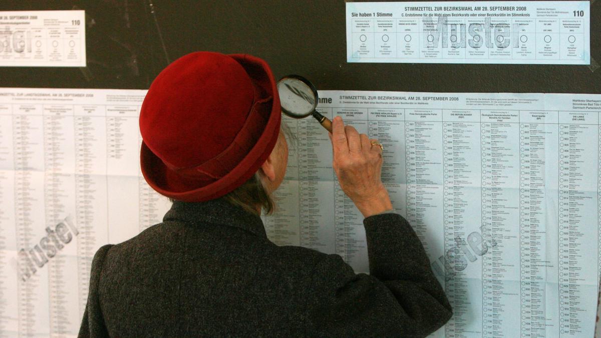 Eine Frau liest mit einer Lupe am Wahlsonntag in Wolfratshausen die ausgehängten Musterstimmzettel.