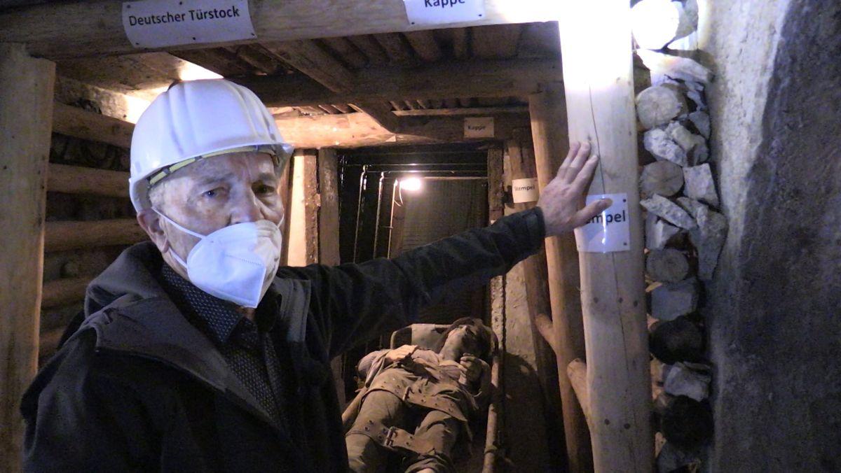 Franz Merkl, ehemaliger Bergmann in Peißenberg, steht in Peißenberg im Bergbau-Stollen, ausgerüstet mit Helm und FFP2-Maske.