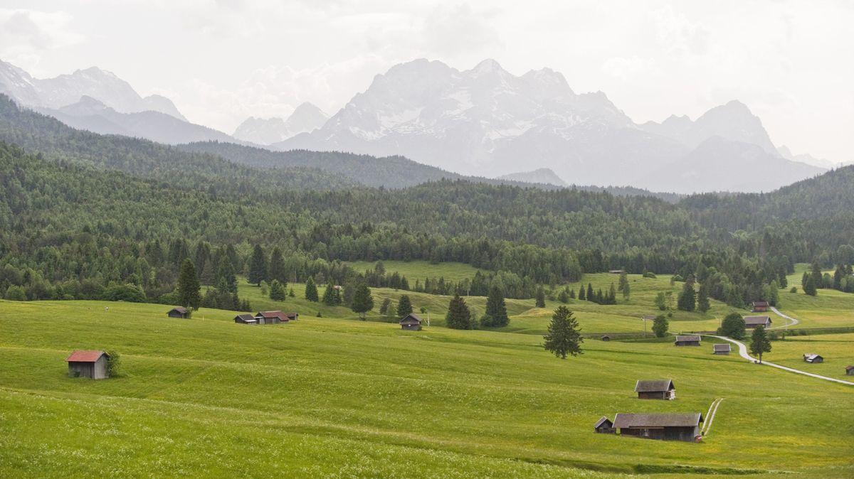 Oberbayerische Landschaft mit Bergen, Wald, Wiesen und Hütten