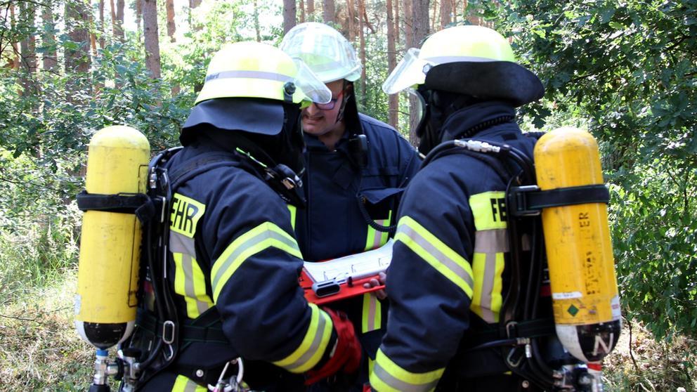 Drei Feuerwehrleute besprechen ihren Einsatz im Wald | Bild:picture alliance/Geisler-Fotopress