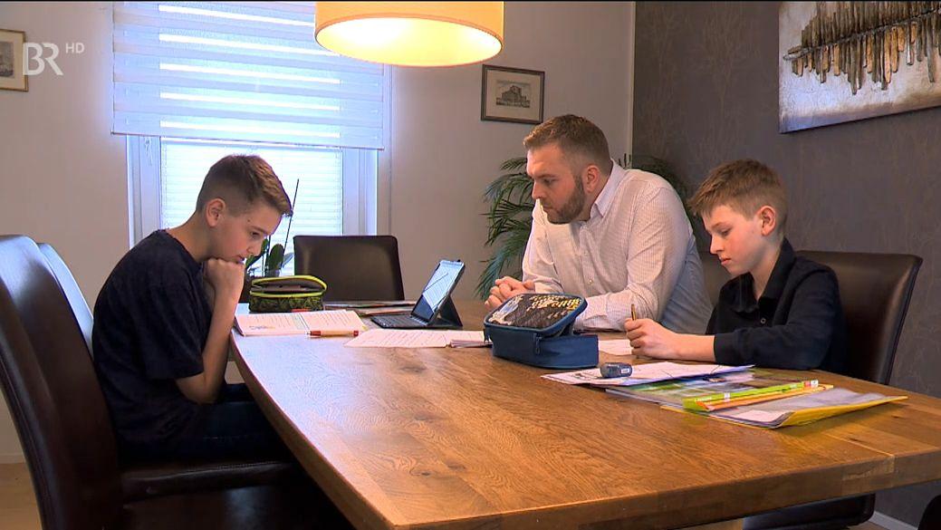Zwei Schüler sitzen mit ihrem Vater an einem Tisch, schauen in ihre Bücher und schreiben, ein Tablet ist aufgeklappt.
