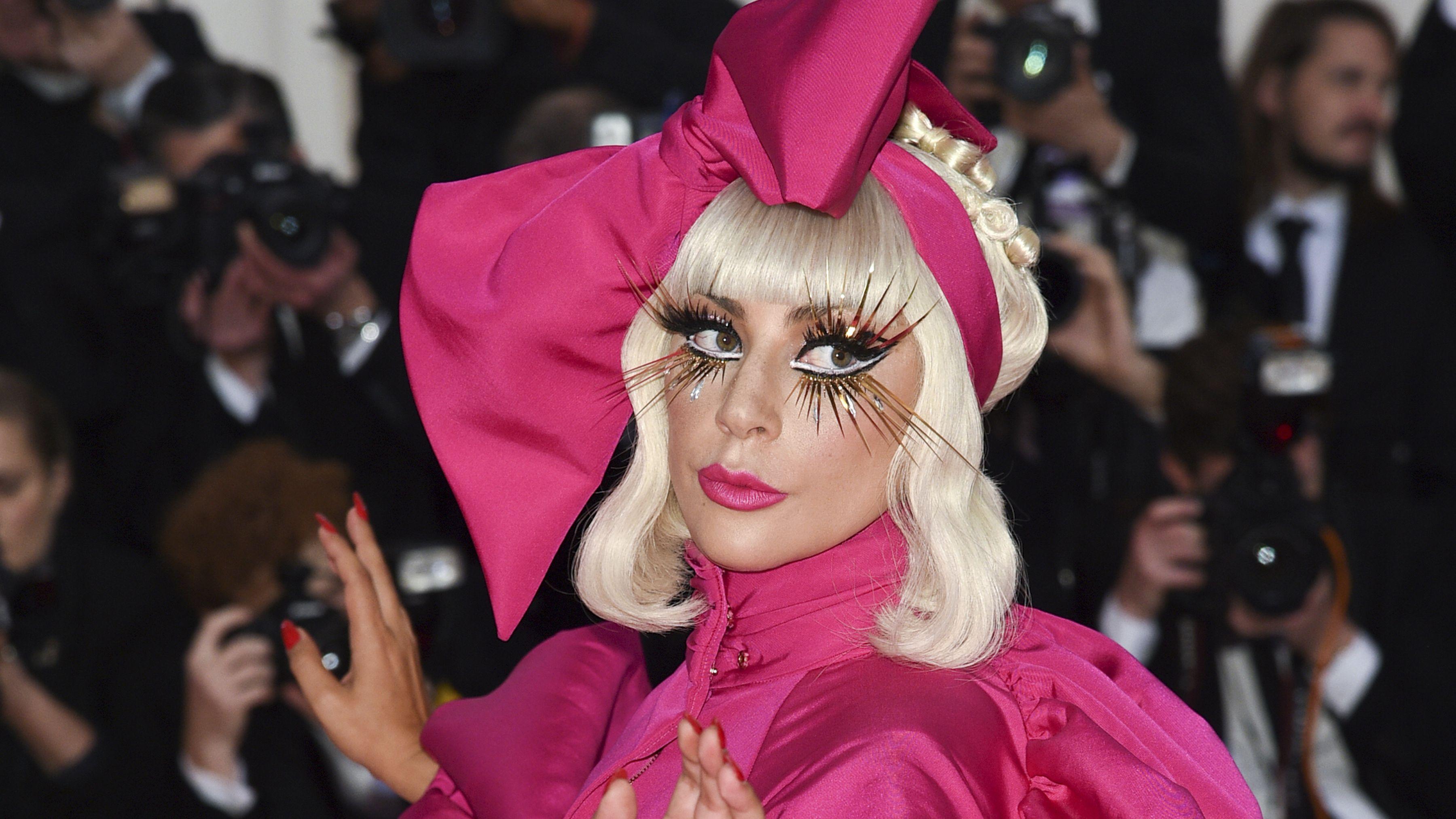 Lady Gaga im pinken Satin-Kleid mit Puffärmeln und riesiger Schleife am Kopf, erinnert an eine Disney-Figur. Auffälliges Augen-Makeup.