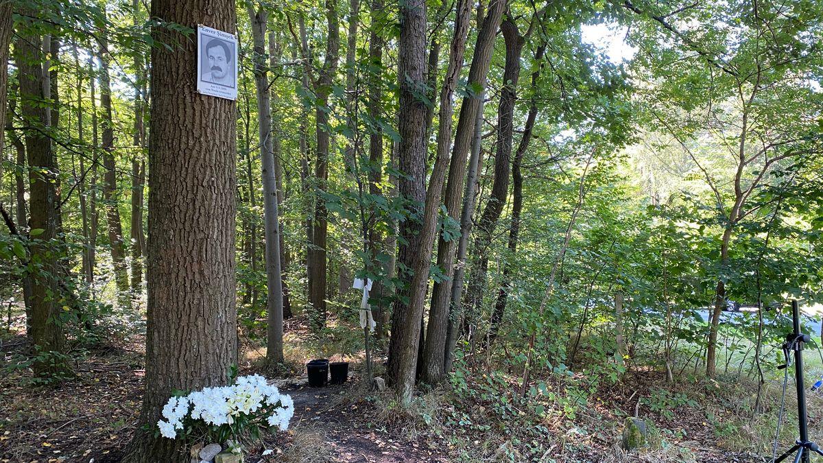 Weiße Blumen lehnen an einem Baum. Am Baumstamm ist ein Foto von Enver Şimşek befestigt.