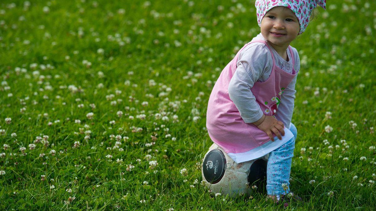 Kleines Mädchen, auf einem Fußball sitzend