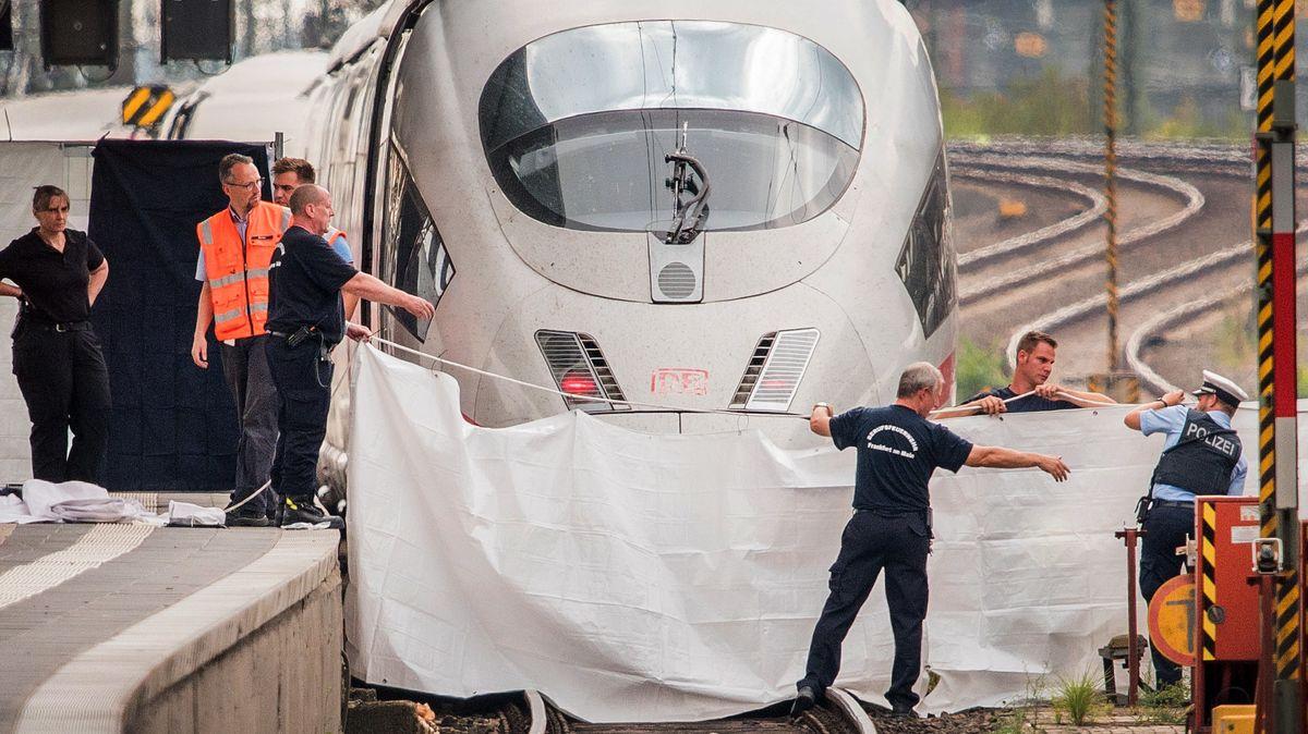 Polizisten und Feuerwehrleute spannen am 29.07.2019 im Hauptbahnhof eine weiße Plane als Sichtschutz vor einen ICE. Ein achtjähriger Junge ist im Frankfurter Hauptbahnhof von einem Mann vor einen einfahrenden ICE gestoßen und getötet worden.
