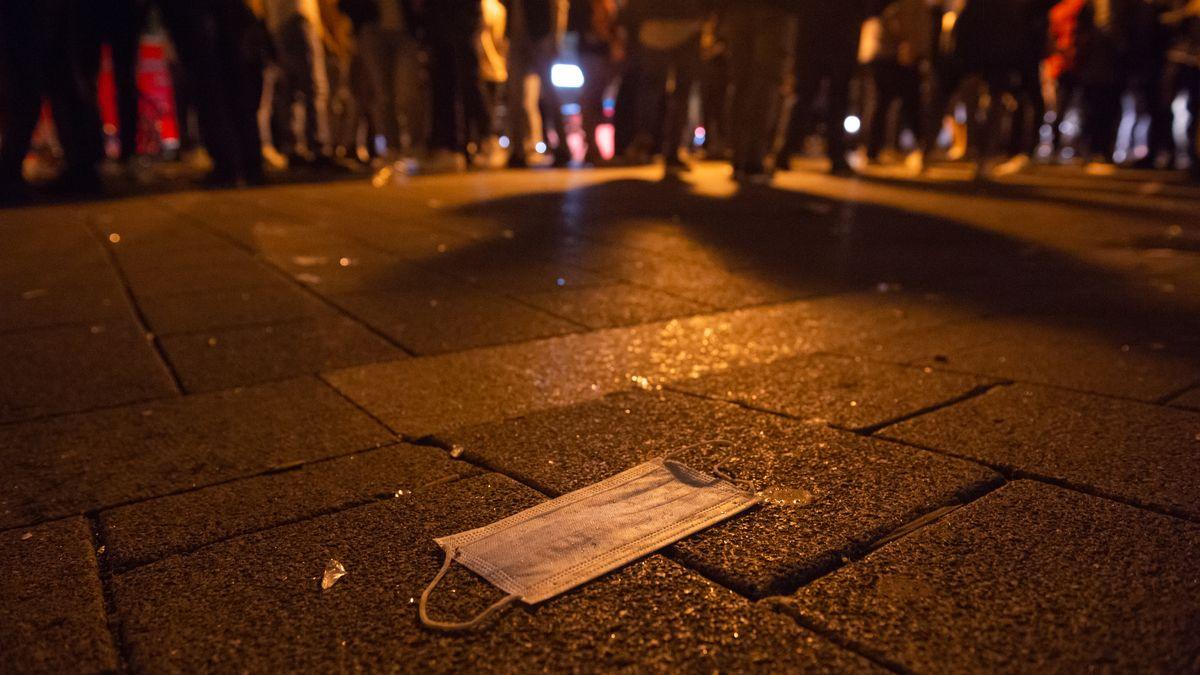 Eine Menschenansammlung nachts in einer Stadt. Auf dem Boden liegt eine Maske. (Symbolbild)