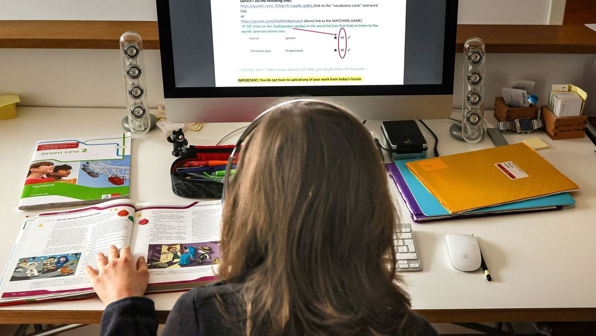 Ein Kind mit Kopfhörer sitzt vor einem Bildschirm, daneben liegen aufgeschlagene Schulbücher.