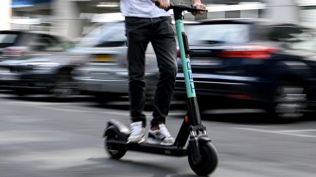 Ein Mann fährt mit einem E-Tretroller auf der Straße.