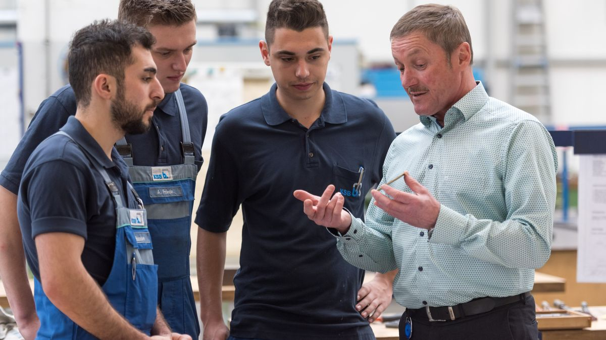 Ein Ausbildungsleiter spricht mit vier Auszubildenden in der Werkstatt.