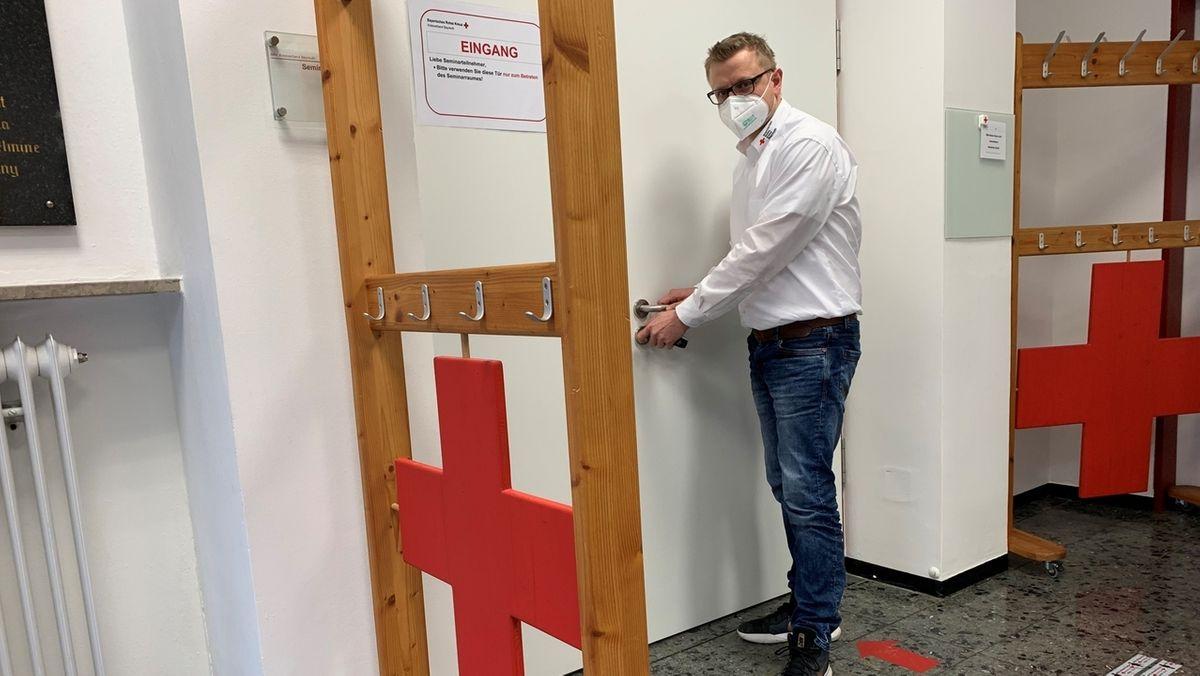 Ein Mann mit Mund-Nasen-Schutz sperrt eine Tür zu, danaben das Rote-Kreuz-Zeichen.