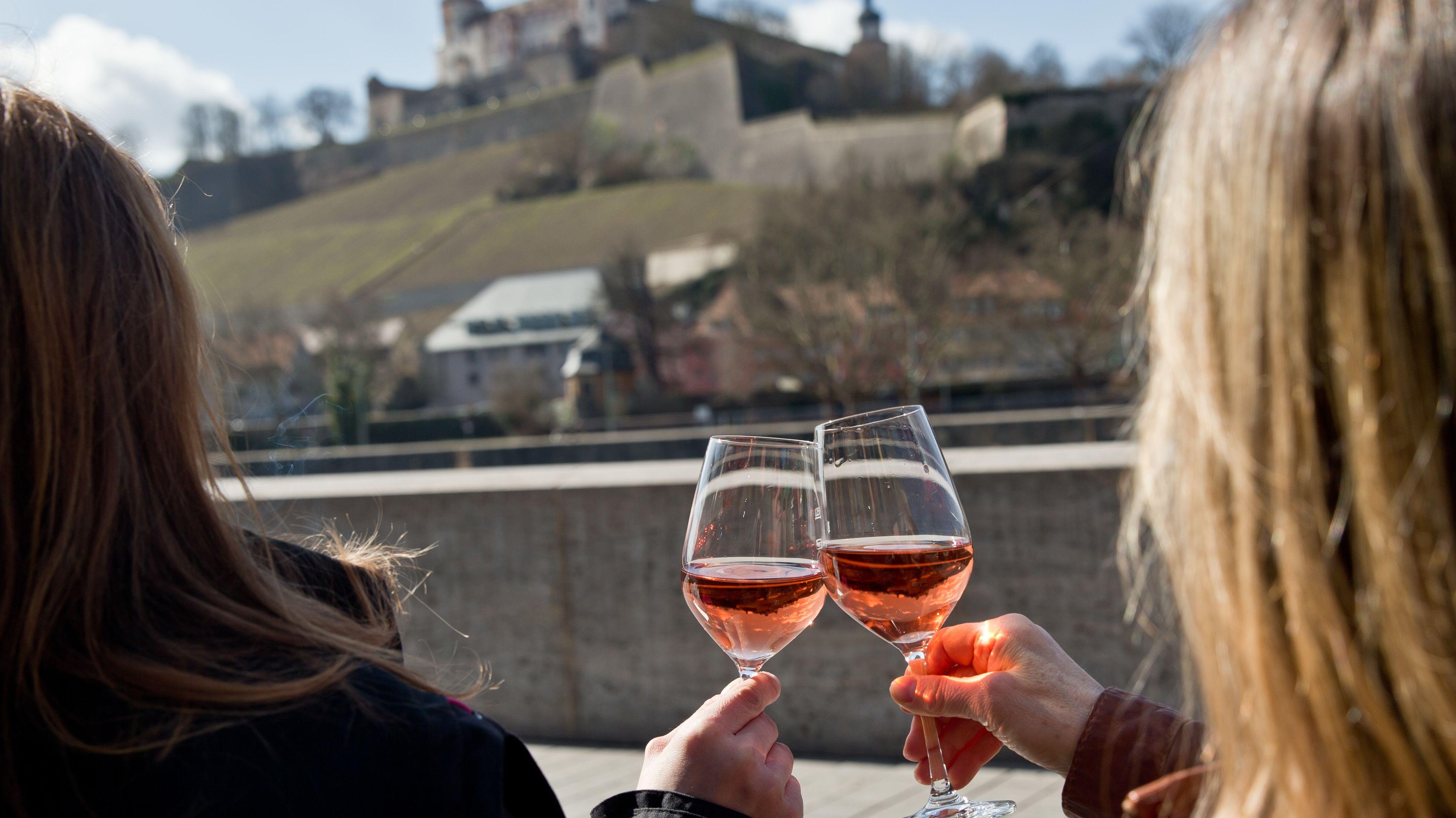 Zwei Frauen stoßen mit Wein an.