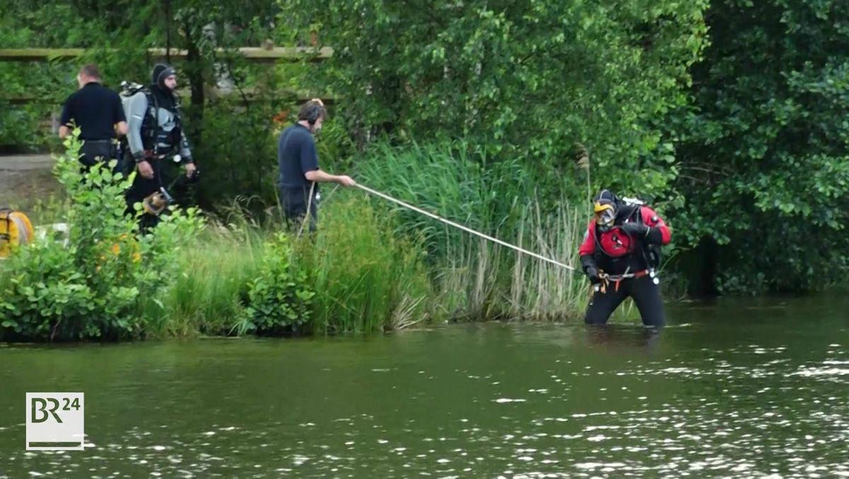 Ein Taucher steigt in den Badesee, über eine Leine wird er von Männern am Ufer gesichert.