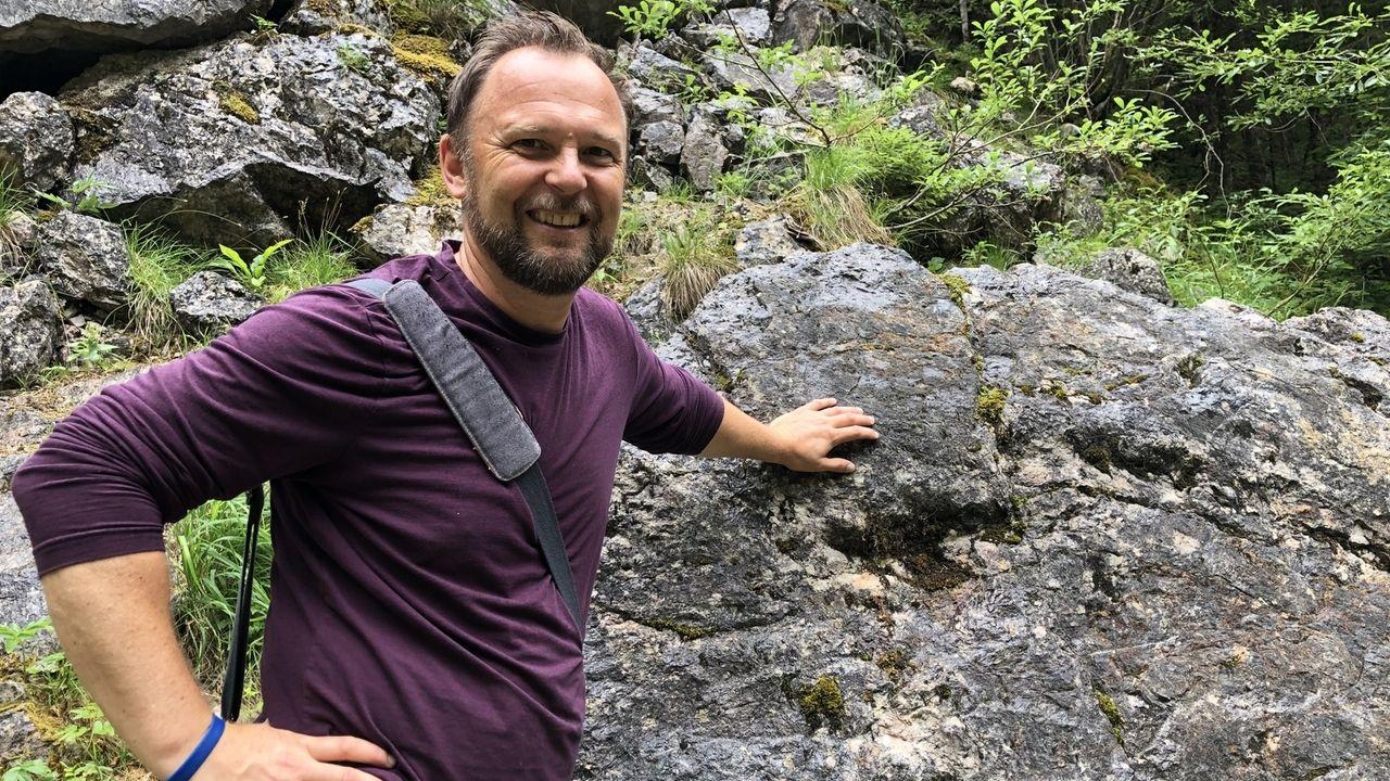 Markus Richter steht vor einem Felsen