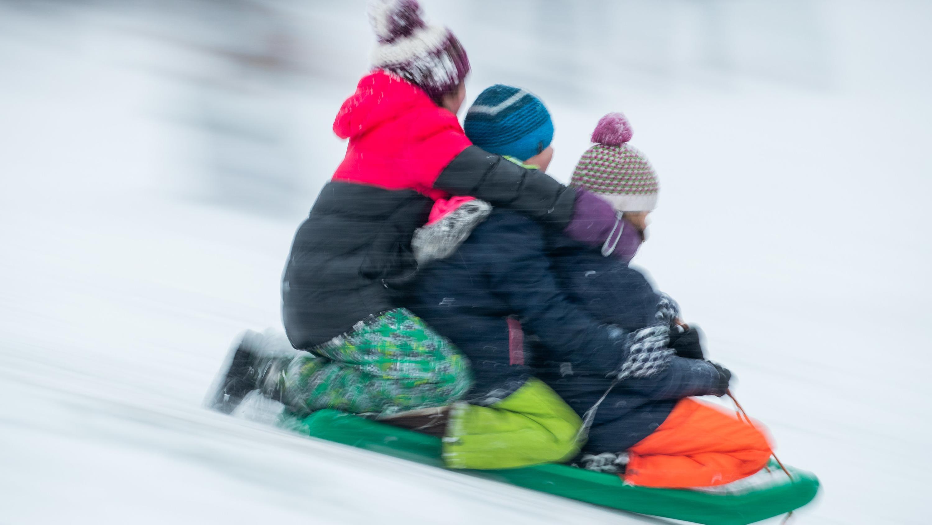 Bayern, Nürnberg: Kinder rutschen auf einem Schlitten einen mit Schnee bedeckten Hügel abwärts
