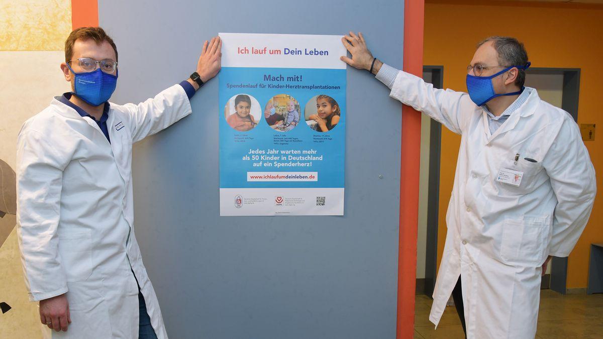 """Dr. Christian Heim und der Leiter der Kinderherzchirurgie des Uni-Klinikums Erlangen Professor Robert Cesnjevar. am Plakat für die Aktion """"Ich lauf um Dein Leben""""."""