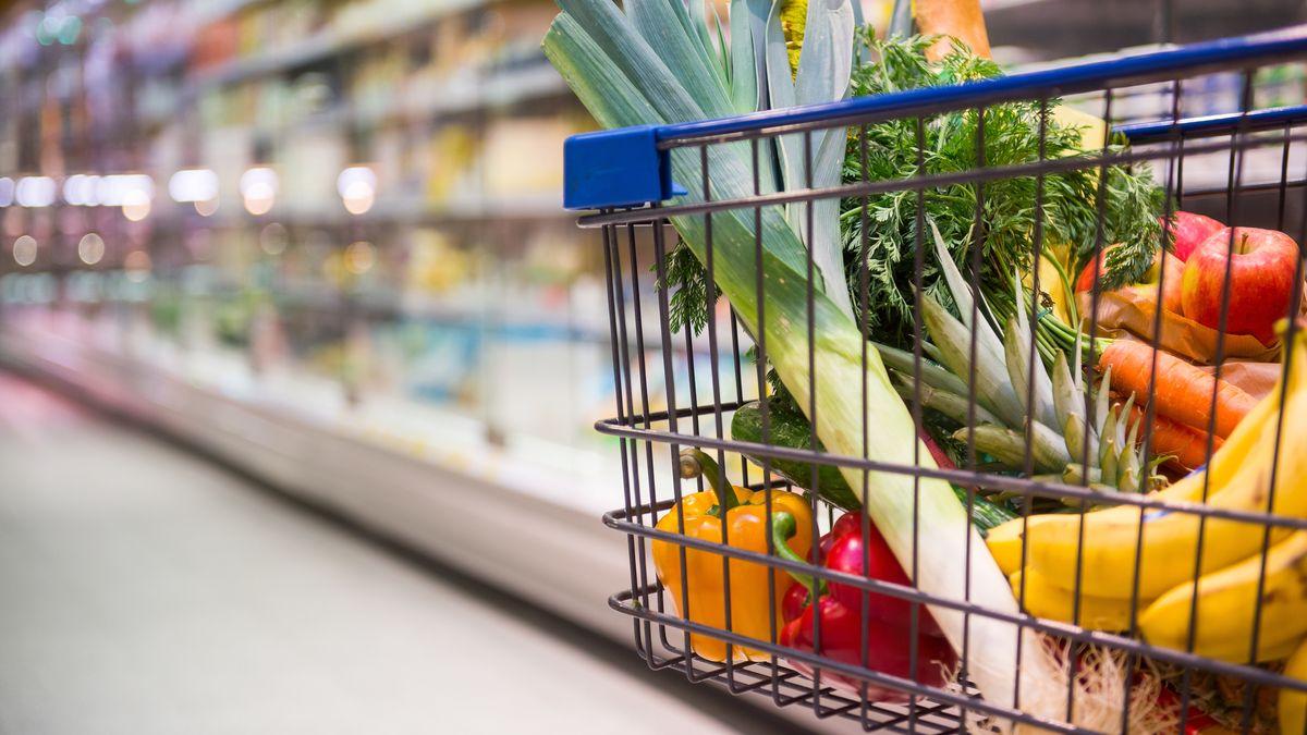 In einem Einkaufswagen liegen Obst und Gemüse. Im Hintergrund sieht man das Kühlregal mit Milchprodukten