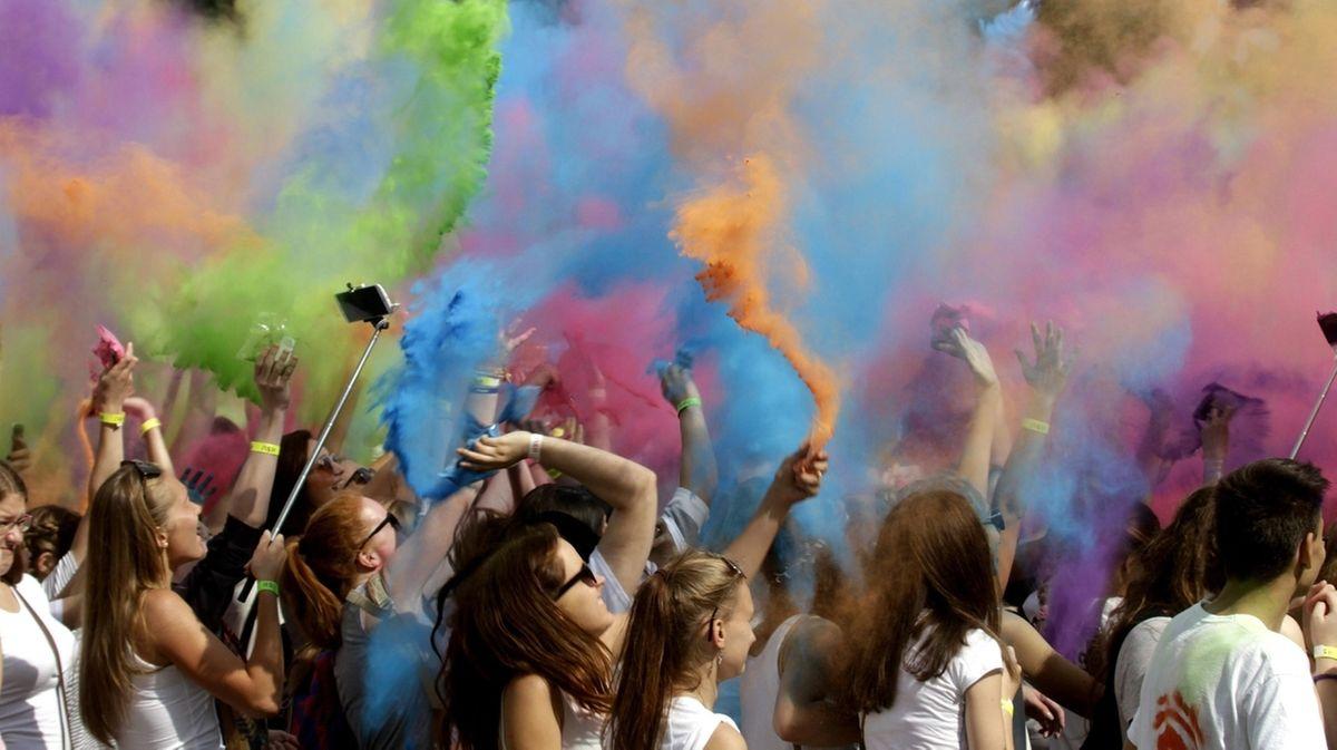 Menschen werfen anlässlich des Holi Colour Festivals 2016 in Riga, Lettland,buntes Pulver in die Luft beim Holi Colour Festival