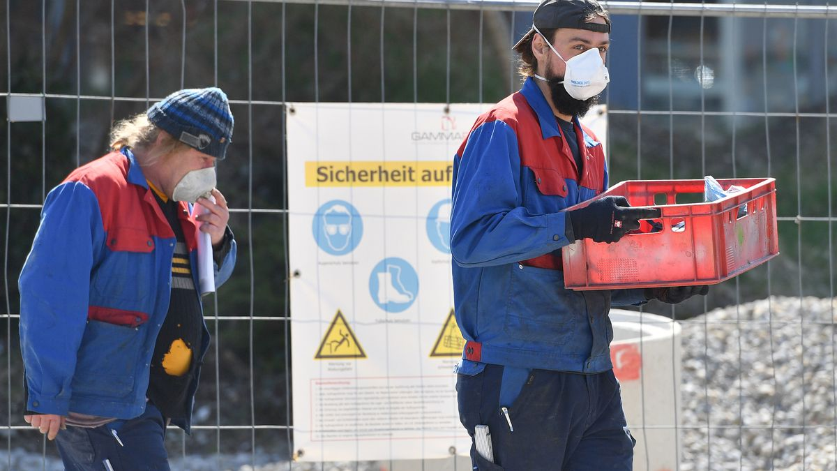 Zwei Bauarbeiter tragen Mundschutz