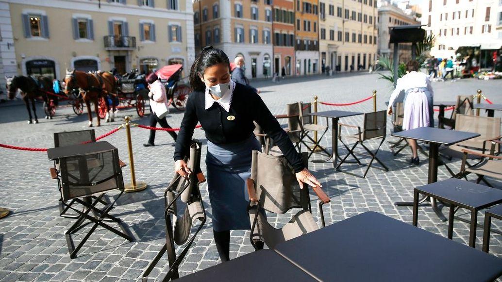 Eine Bedienung mit Mundschutz bei einem Café in Rom
