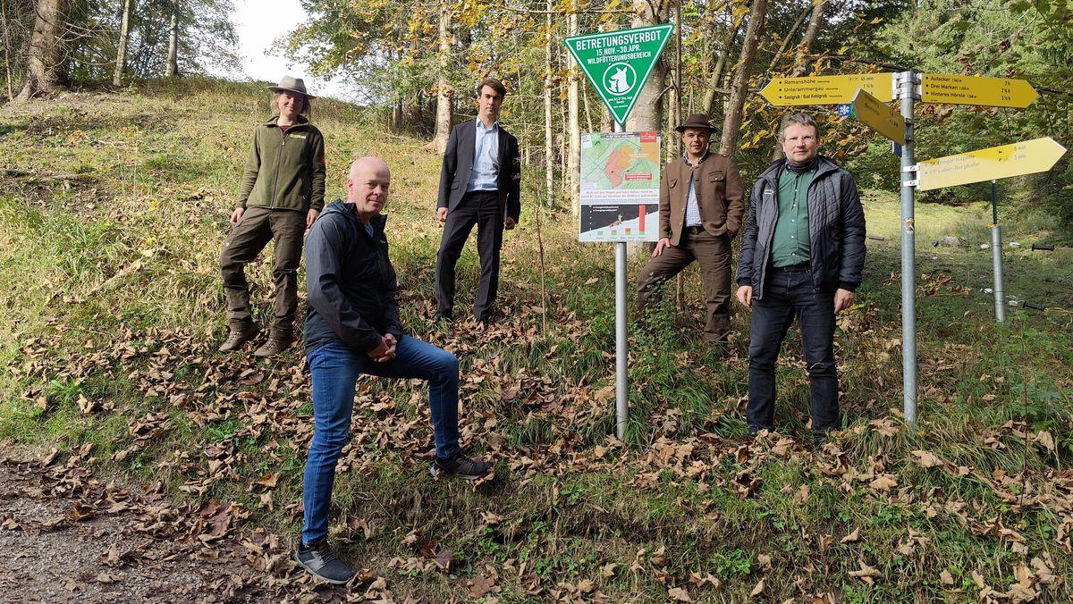 Naturparkranger und Jäger aus den Ammergauer Alpen posieren vor einem Schild, das ein Betretungsverbot im Winter ankündigt