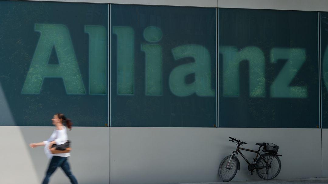"""Eine Frau geht am Schriftzug """"Allianz"""" an einem Gebäude des Versicherungskonzerns vorbei."""