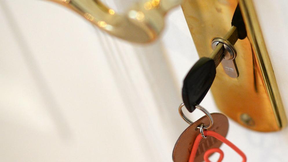 Ein Schlüssel steckt im Schloss einer Airbnb-Ferienwohnung. Die Online-Buchungsplattform Airbnb muss der Stadt München die Namen und Adressen von Anbietern illegal genutzter Ferienwohnungen preisgeben. | Bild:Jens Kalaene/ZB/dpa