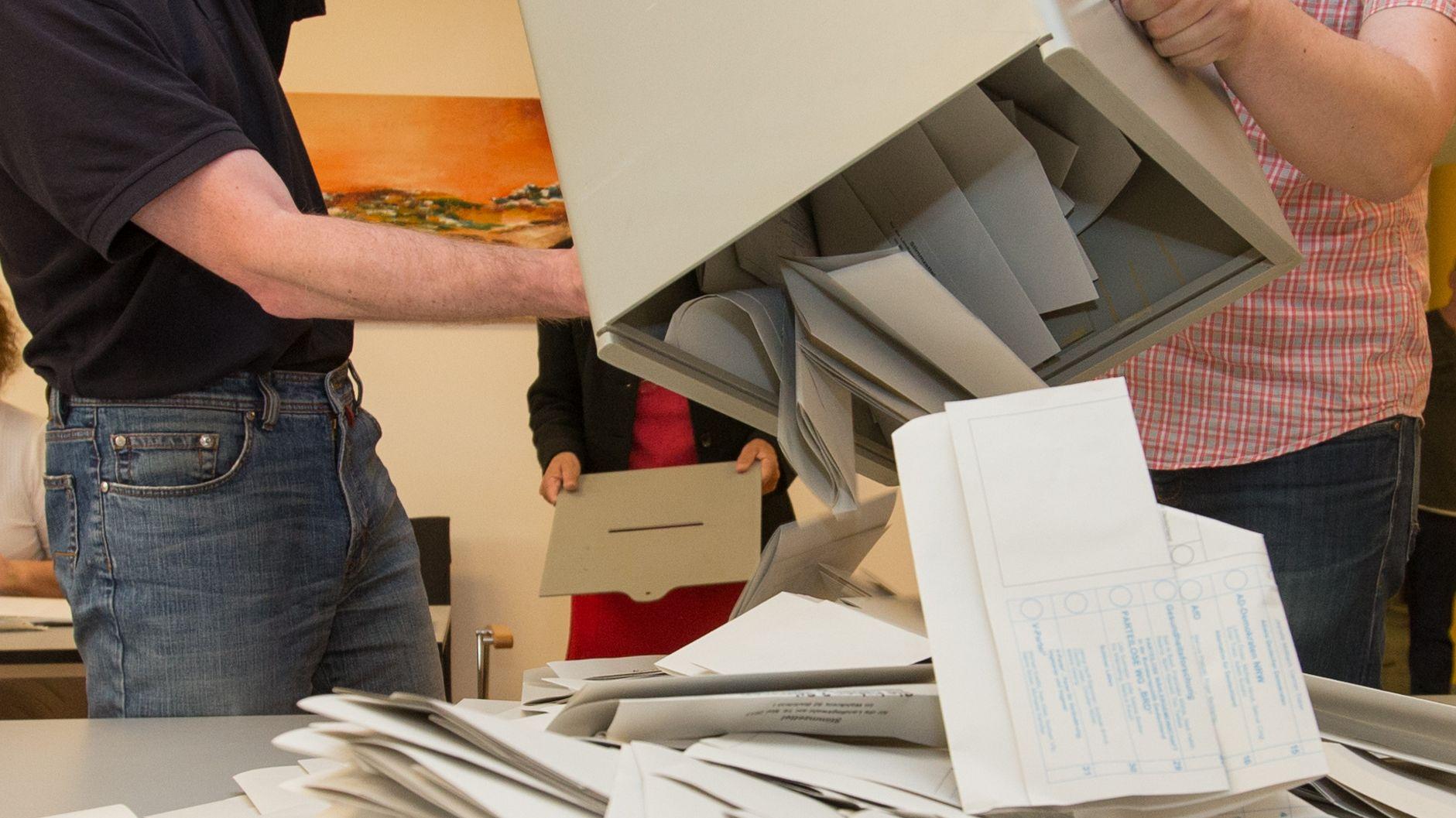 Wahlhelfer leeren eine Urne mit Stimmzetteln