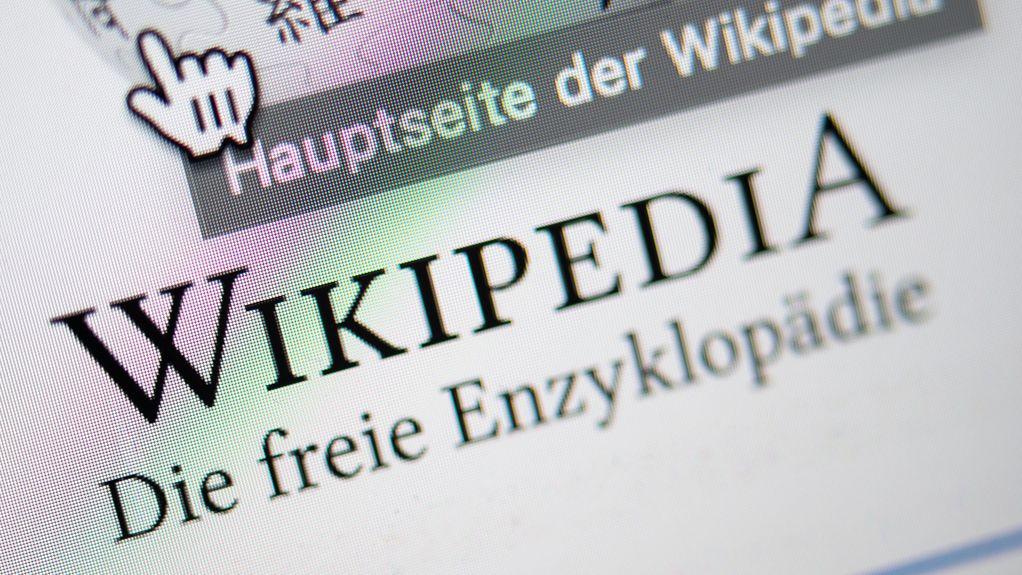 """Schriftzug """"Wikipedia"""" auf einem Computerbildschirm mit Maus-Symbol"""